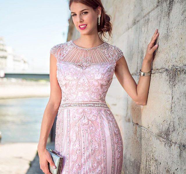 Nainen vaaleanpunaisessa juhlamekossa, kädessä käsilaukku