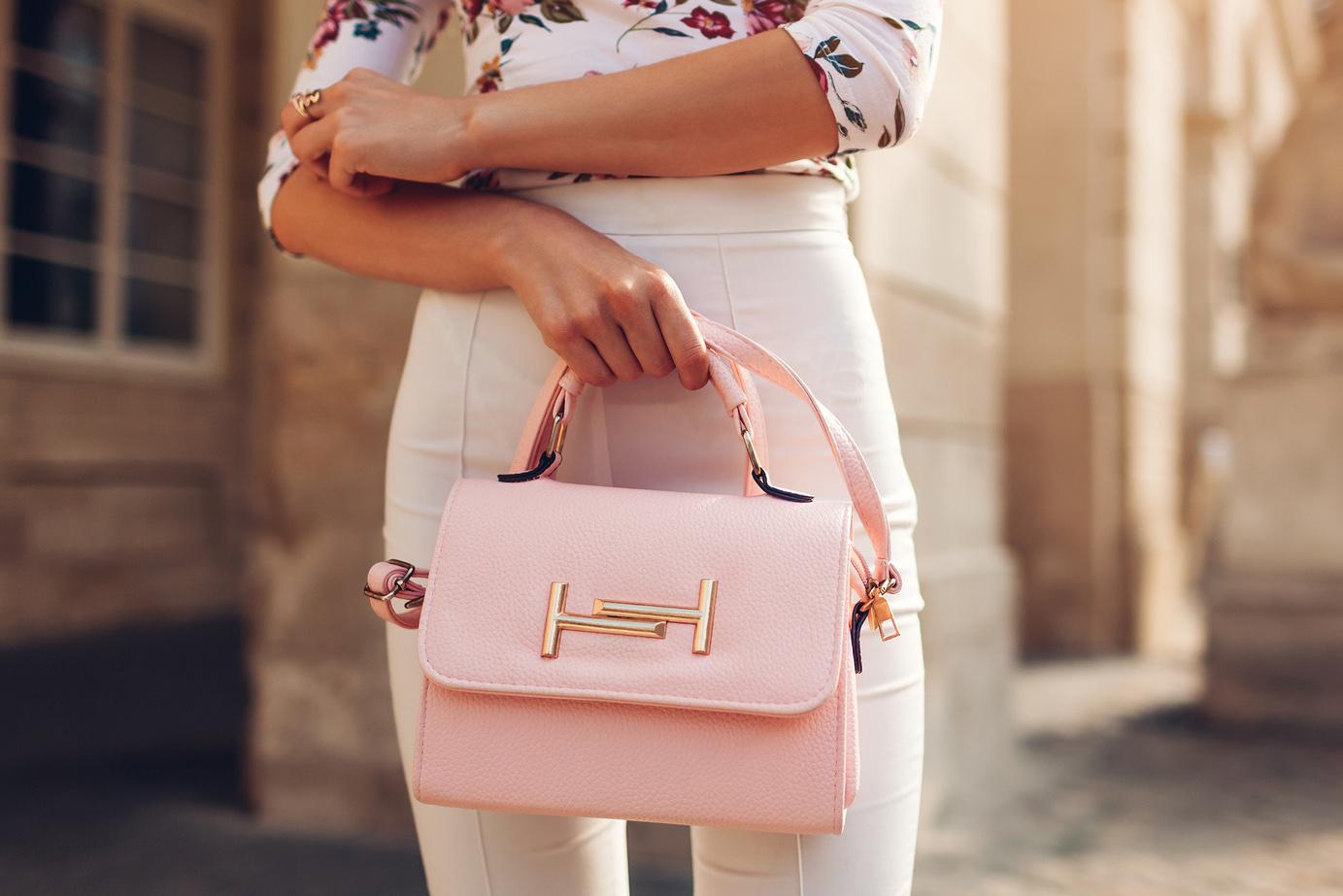 Kuva vaaleanpunaisesta laukusta tyylikkään naisen kädessä